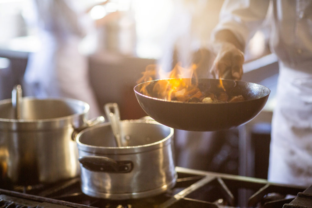 Chef tossing stir fry over large flame in commercial kitchen