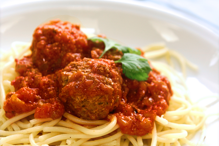 Plate of meatball spaghetti in tomato sauce and garnishing of parsley.